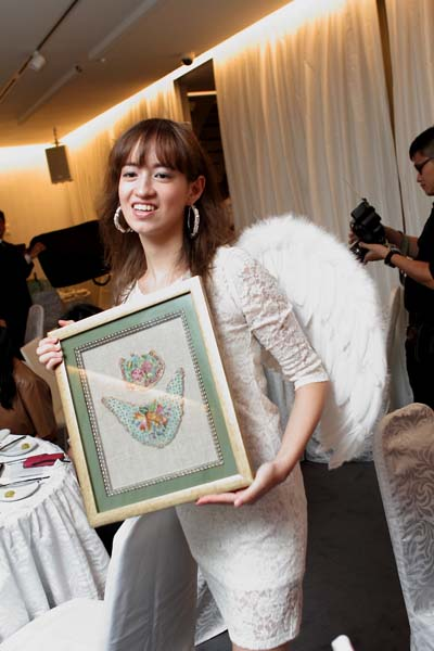 An angel model with an intricate piece of antique beadwork for auction