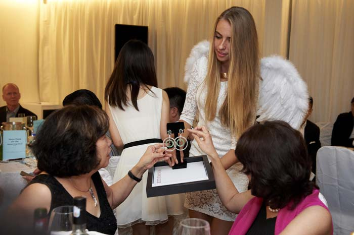 Sabrina displaying the donation item from Elegance Club to the esteemed guests