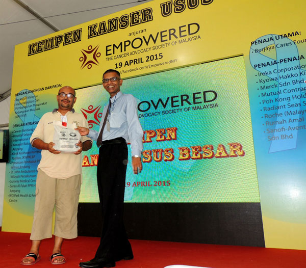 A quiz winner presented with a charming gift by Dato' Dr. Fitjerald